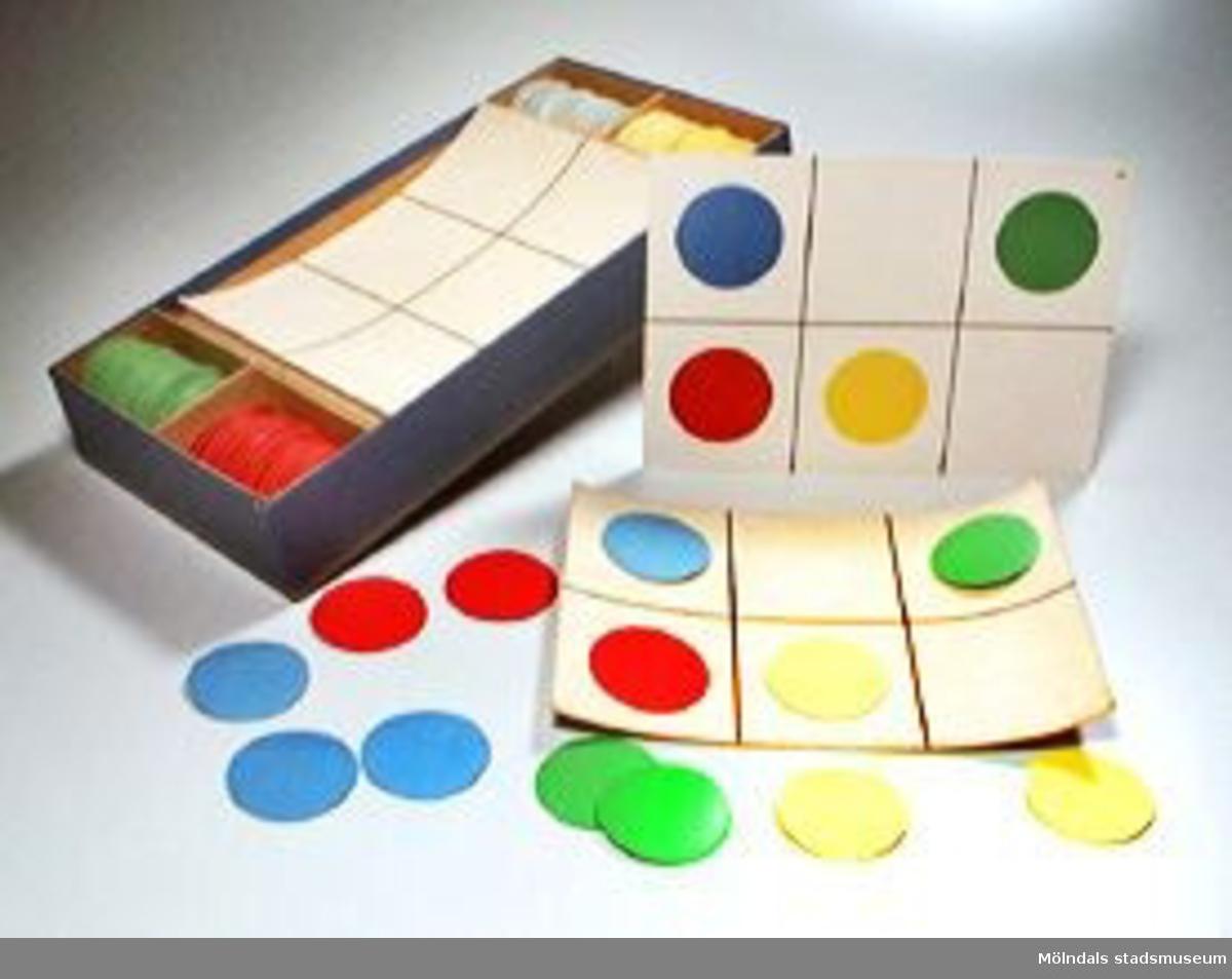 Prickspel. Består av 15 st elevplattor och 30 st lärararplattor. Till hör cirkelplattor i färgerna: rött, grönt, blått och gult (60 st av varje). Plattorna och cirklarna har kardborreliknande tyg, för att fästa mot varandra. Spelet går ut på att läraren visar upp en platta med ett visst mönster (av cirklar i olika färger) för eleverna. De får sedan lägga samma mönster, utan förebild på egna arbetsplattor. Det saknas en röd och en gul cirkelplatta. Spelet förvaras i en gråblå pappkartong. Spelregler i lockets insida.
