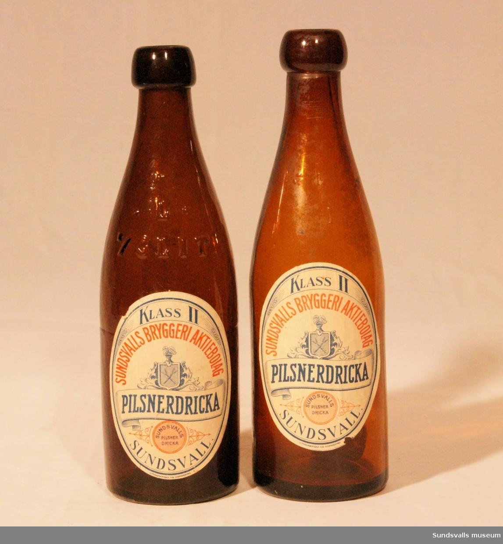 Tre flaskor tillverkade på Sundsvalls bryggeri aktiebolag. Flaskorna är bruntonade och har etiketter där texten lyder 'KLASS 2, SUNDSVALLS BRYGGERI AKTIEBOLAG, PILSNERDRICKA, SUNDSVALLS PILSNERDRICKA, SUNDSVALL'. Etiketterna har blå och röd text och motiv på vit botten och de är tillverkade hos Lithografiska AB i Norrköping.