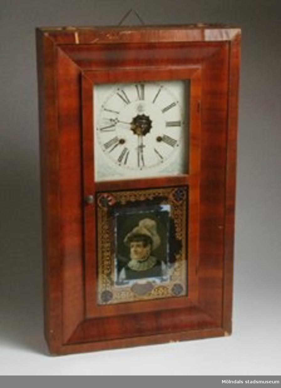 Väggklocka med vit urtavla med romerska siffror. Boett av trä. Glasad pendellucka med dekorbild, porträtt av en dam med hatt. Omgiven av guldfärgad dekor mm. Uppklistrat papper med text.