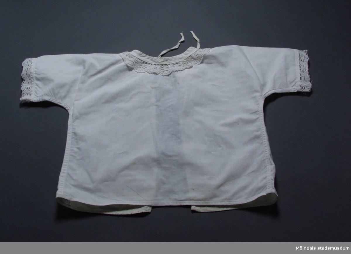 Spädbarnsskjorta i vit bomull med spets kring halsringning och ärmar.