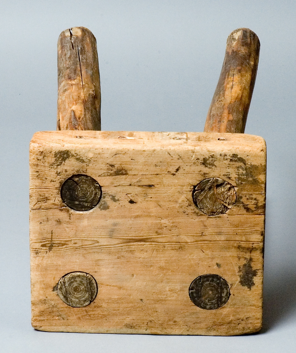 Pall, handgjord av trä, furu. Fyrkantig sits med fyra genomgående itappade ben.  Skrivet under sitsen: Skansens rekvisita (Delsbogården) BOLLNÄS.
