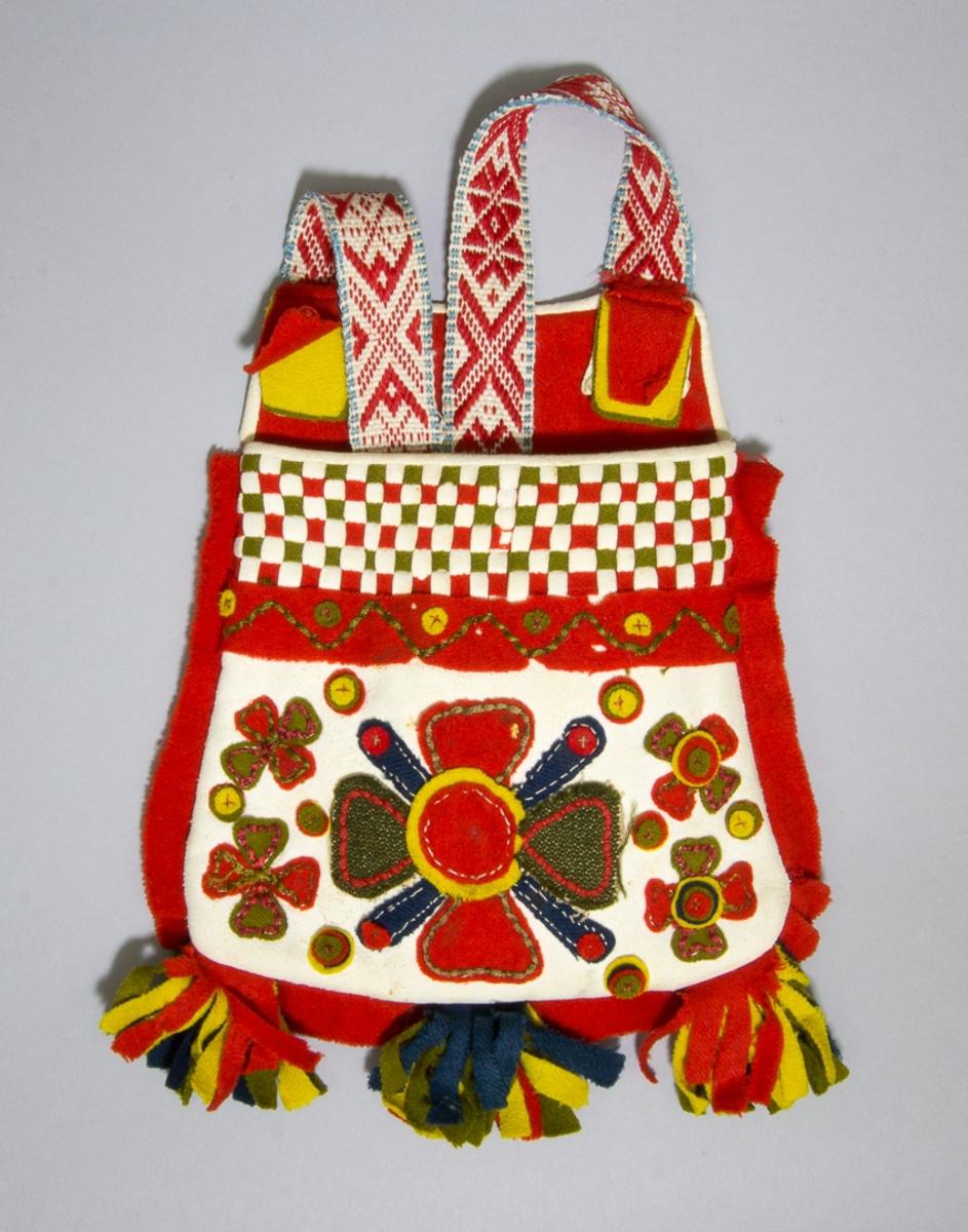 """Kjolsäck till dräkt för kvinna från Rättviks socken, Dalarna. Modell med avskuret framstycke. Tillverkad av vitt sämskskinn med applikationer av rött, gult och mörkblått kläde samt grönt halvylletyg, fastsydda med efterstygn och läggsöm. Centralt placerad blomma omgiven av mindre blommor och rundlar. Sparsamt broderi utfört med rött och grönt bomullsgarn: läggsöm. Ovanför applikationen en remsa rött kläde fastsydd med läggsöm, därovan en """"grind"""" flätad av smala remsor rött och grönt kläde samt vitt sämskskinn, kantning av samma skinn. En remsa rött kläde inlagd i sido- och bottensömmarna. I bottensömmen även tre tofsar klippta av rött, gult grönt och blått kläde. Foder av rött fabriksvävt bomullstyg, kypert. Överstycke av rött kläde. Bakstycke av vitt fårskinn. Kantning upptill av vitt sämskskinn. Axel- eller midjeband handvävt, med plockat mönster av rött ullgarn på vit botten av lin, dock av en annorlunda typ. Vid fästena på överstycket sitter två tofsar tillverkade av små lappar kläde i rött, grönt och gult."""