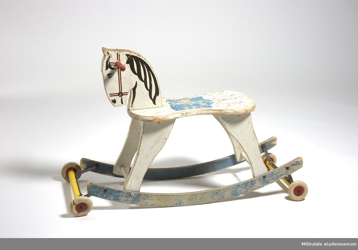 En liten gunghäst i trä, målad i vitt, blått, gult och rött. Försedd med fyra små trähjul, vilket gör att hästen kan rulla. Hjulaxeln är uppfällbar, och då blir hästen åter gungbar. Gunghästen är använd av Mikael, Henrik, Johan, Frida och Robin enligt märkning på hästen.2 av 4 hjul är spruckna, färgen flagnadGåva av vårdpersonal vid äldreboende 2006.