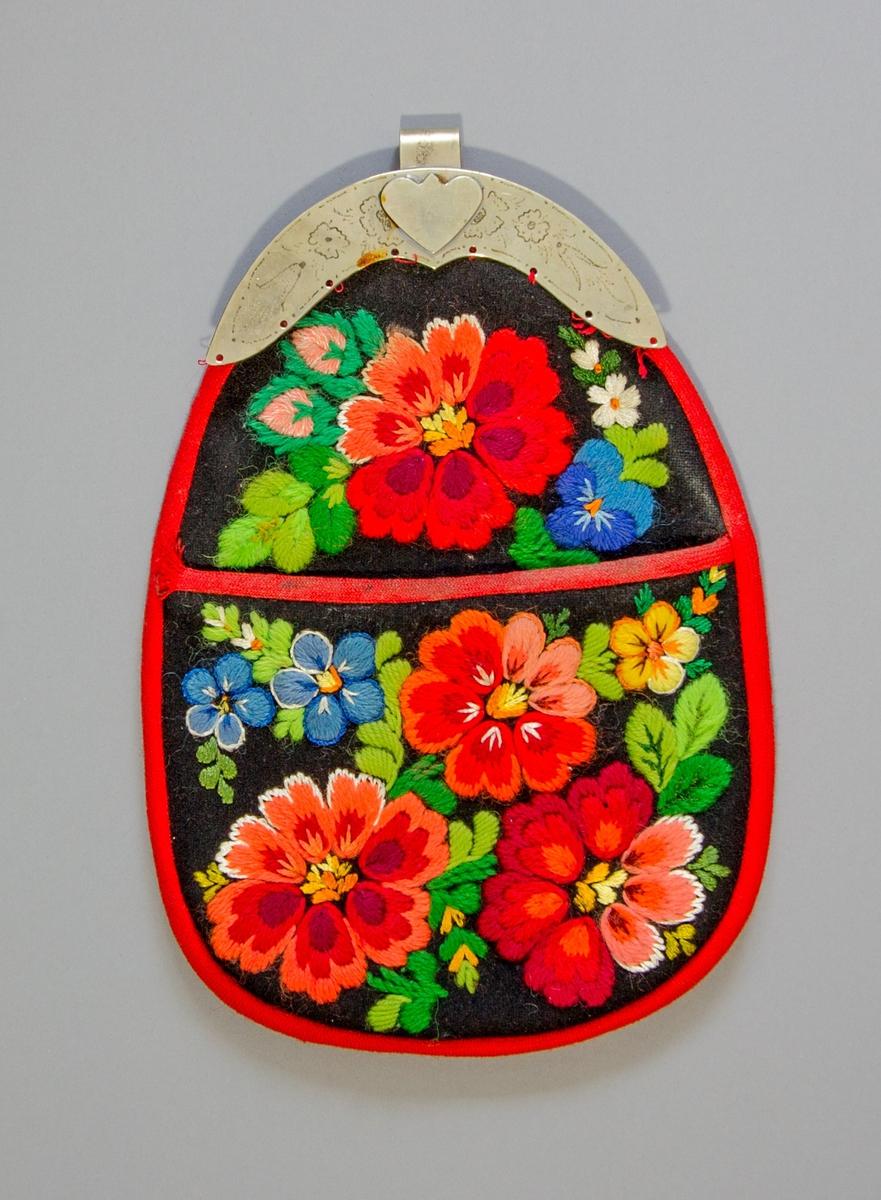 Kjolsäck till dräkt för kvinna från Dala-Floda socken, Dalarna. Modell med avskuret framstycke. Tillverkad av svart ylletyg, kläde, med broderier av ullgarn och bomullsgarn i många färger; plattsöm, stjälksöm och sticksöm. Motiv av blommor och blad, även broderat på överstycket. Kantat runtom med rött diagonalvävt fabrikstillverkat band av ull. Foder av grålila fabrikstillverkat bomullstyg, tuskaftsvävt. Bakstycke av samma tyg. Bygel tillverkad av vitmetall med graverat mönster av blommor, fast hake.