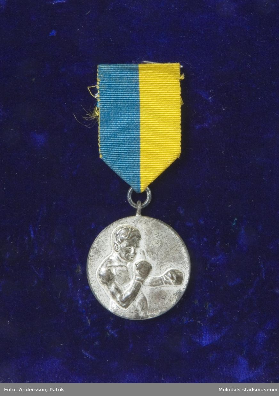 Idrottsmedalj, tilldelad tungviktsboxare Henry Nicklasson. Försilvrad medalj med avbildad boxare på framsidan. På baksidan, avbildad lagerkrans samt texten Box-serien 34. Medaljen hänger i ett blågult sidenband.