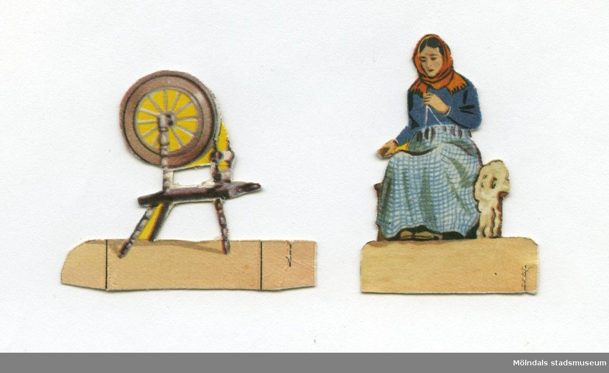 """Figurer av papp, från 1950-talet. Den ena föreställer en kvinna i hellång kjol och sjalett som sitter och spinner, den andra figuren, en spinnrock. Figurerna har troligtvis använts i en papp- eller modellteater. """"Modellteatern [...] är en form av dockteater som blev populär i Europa under 1800-talet, då ungdomar fick möjlighet att i förminskad skala efterbilda samtida uppmärksammade teateruppsättningar. De tvådimensionella dekorelementen och figurerna skars ut ur förtryckta, färglagda ark. Denna form av dockteater blev som ett borgerligt familjenöje, speciellt populär i Tyskland, Danmark och Storbritannien."""" -Utdrag ur Nationalencyklopedin."""