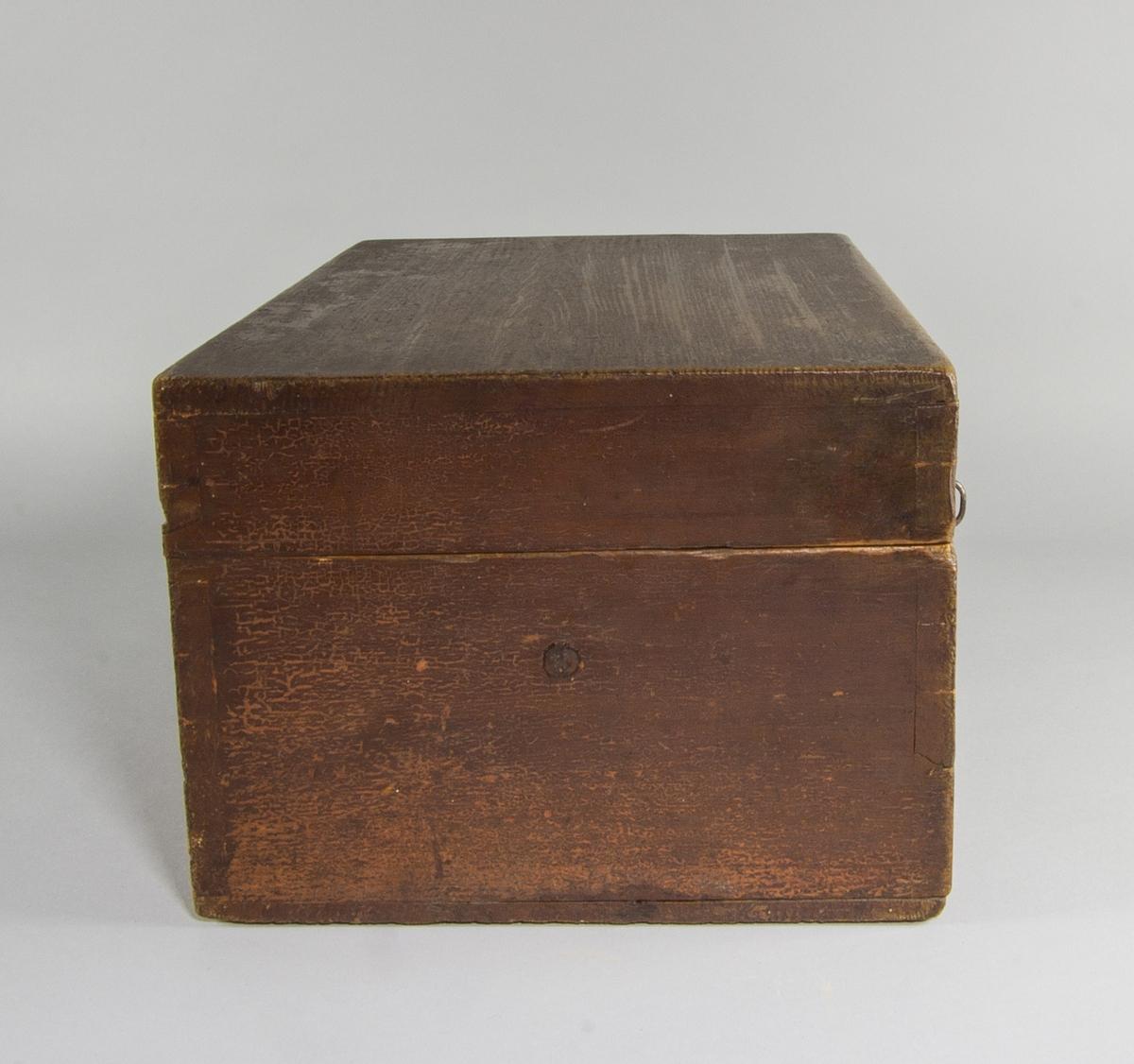 Sockerskrin i målat trä. Rektangulärt till formen, försett med fällock, lås och nyckel. Undertill låda. Bottnet till skrinets övre del utgörs av platta av perforerad plåt. Över detta trälist varpå sockerkniv med svarvat skaft är monterad. Uppsamlingslådan undertill är utdragbar och försedd med metallknopp.
