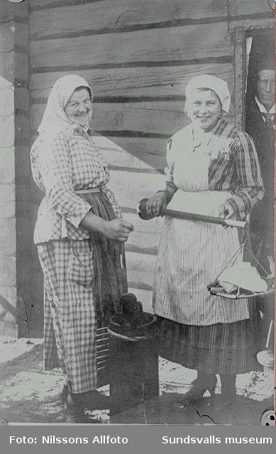 Kvinnor framför ev visthusbod, med smörkärna och besman. I dörröpningen står en man. Bilden tagen troligen från Gösta Nilssons tid i Västergötland.