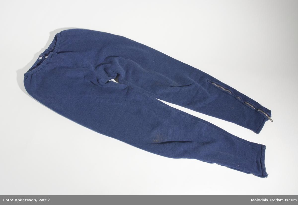Träningsoverallsbyxa från 1970-talet.Det finns också en tillhörande tröja (MM04881:1).Träningsoverallen användes troligtvis av givarens son Jonas (född 1970). Den kan också ha användts som mysdress.Byxorna är mörkblåa och har resår i mijan. Nedtill på byxbenen finns en dragkedja på varje ben. Byxorna har också en bakfika till höger.Tygetiketten med storlek, material eller tvättråd som brukar vara fastsydd inuti byxorna baktill är bortsliten.MåttLängd: 820 mmMidjebredd: 200 mmBenlängd: 575 mm, Bredd: ca. 220 mmLängd på dragkedja: 260 mm