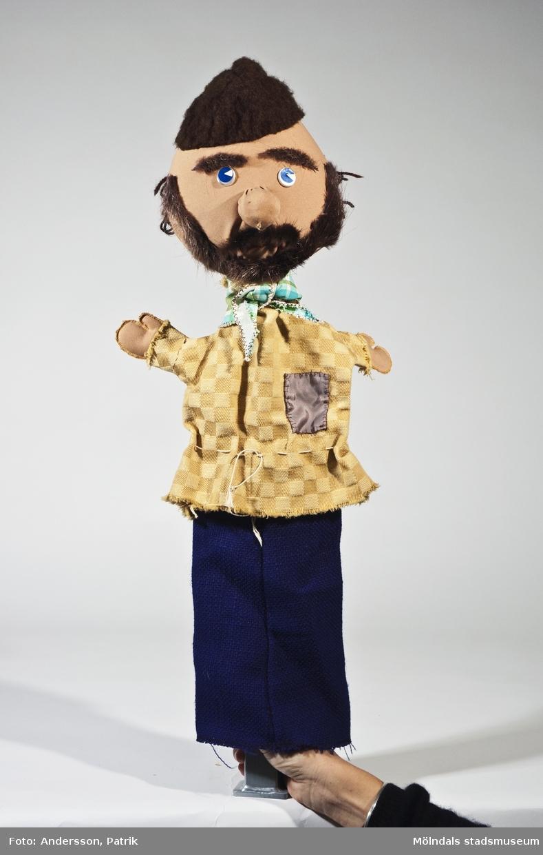 """Rövare ur sagan om """"Stadsmusikanterna från Bremen"""". Handdockan har en brun, tovad (?) mössa, skägg och mustasch i päls, schackrutig gul tröja och blå nederdel.Givaren Blanka Kaplan var förskollärare och använde dockteater i sin pedagogik. Hon var ledare för dockteatern """"Tusensköna"""" som spelade klassiska sagor i tjeckisk tradition. Blanka Kaplan är född i Tjeckoslovakien och kom till Sverige 1968. De sista åren före sin pension åkte hon runt i olika förskolor med sina föreställningar.(se bilaga i arkiv)."""
