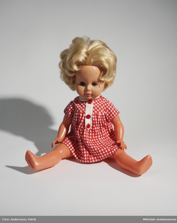 """Docka, tillverkad av företaget Ratti i Italien under 1950 - 70-talet. Dockan Ratti  har ljust hår och har blå blundbara ögon. Hon har en rödrutig kort klänning på sig.På dockans rygg finns loggan """"RATTI MADE IN ITALY"""" och numret """"4 5"""", gjutet i plasten. Nedanför sitter speldosan som ger ifrån ljud när man vänder på dockan. Givaren Ulrika Liljemark fick dockan i julklapp på julafton 1964. Det finns ett tillhörande fotografi (MMF2013:0006), där Ulrika med den nya dockan Ratti är avbildad.MåttLängd: cirka 410 mmMidjebredd: 100 mm"""
