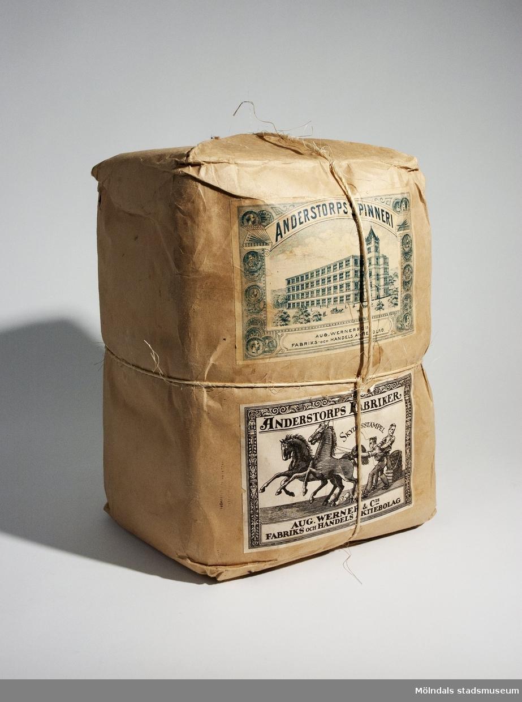 """Ett paket som innehåller vävgarn från Anderstorps fabriker.Vävgarnet är inslaget med brunt papper och har brunt snöre som håller ihop paket. På paket finns 2 st etiketter påklistrade. På dessa etiketter finns texten: """"ANDERSTORPS SPINNERI AUG. WERNER & C IS FABRIKS- OCH HANDELS AKTIEBOLAG."""" och """"ANDERSTORPS FABRIKER SKYDDSSTÄMPEL AUG. WERNER & C IS FABRIKS OCH HANDELS AKTIEBOLAG"""". På etiketterna finns  också teckningar som avbildar fabriken och hästar.På ena kortsidan av paket finns också en svart stämpel: """"16. 2 TRÅDIGT"""".Pakets ägare är Augusta Påsse (född den 5 maj 1874) från Knipered i Lindome. Givare Siv Synnergren från Landvetter.Mått på paketLängd: cirka 300 mm, Bredd: cirka 230 mm, Höjd: cirka 210 mm"""