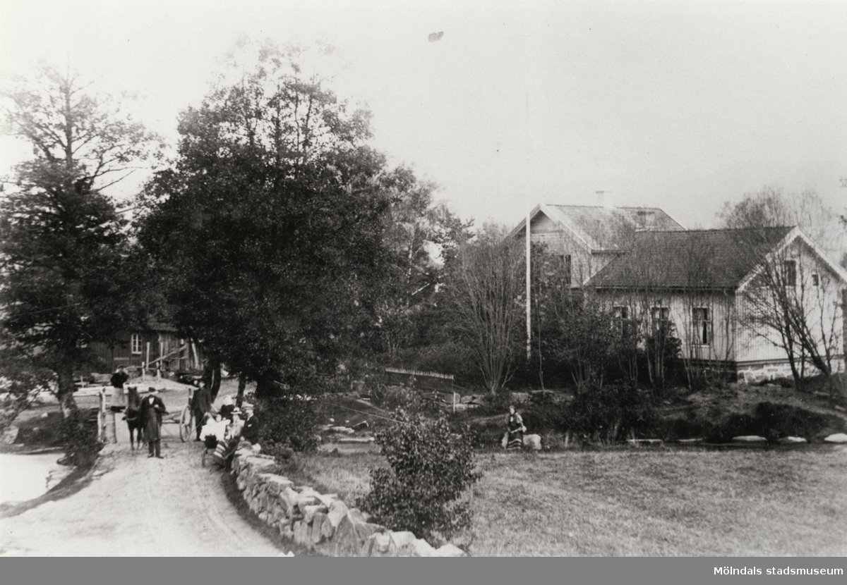Hällesåkers bro i Lindome, 1907. Liten folksamling samt häst med kärra på bro.