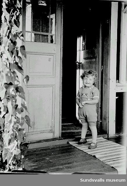 Porträtt, barn står i dörröppningen till bostaden.