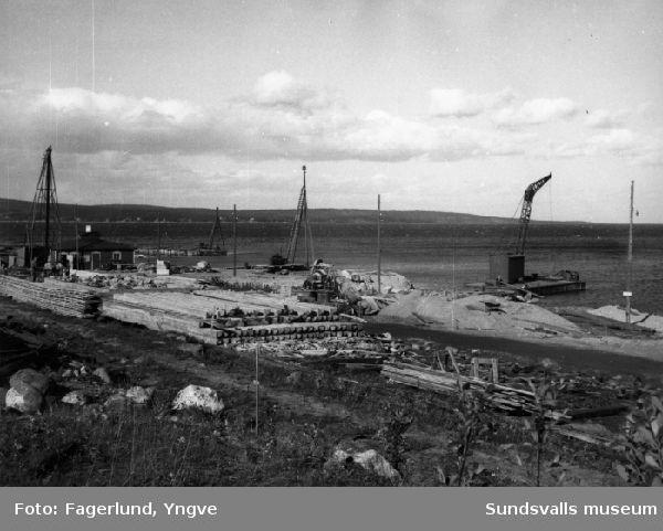 Muddringsarbete i Stockvik inför anläggandet av Stockviksverken. Pålupplag på kajen.