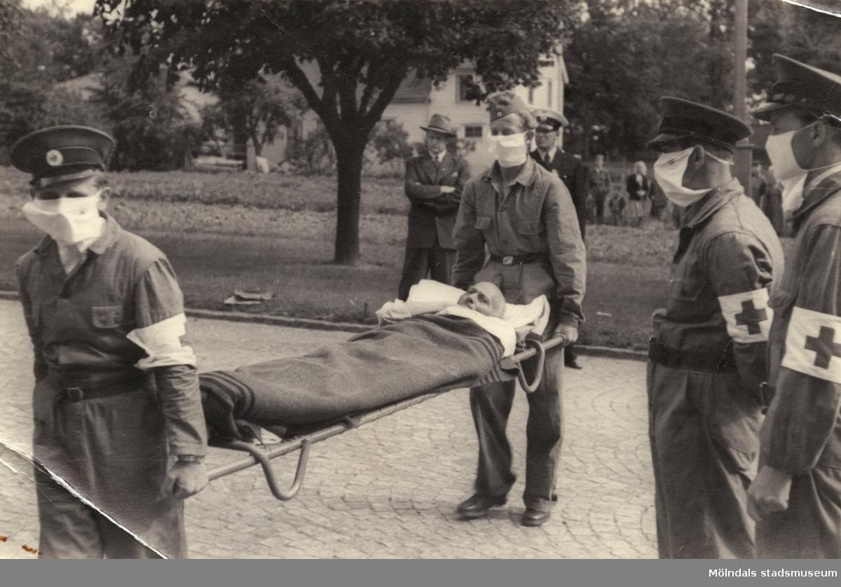 """""""Karantänsförläggning"""" på Kvarnbyskolan för flyktingar från koncentrationsläger i Tyskland 1945. En flykting bärs in på bår av Röda Korsets personal."""