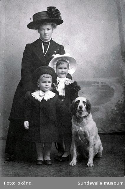 Barnen Ando och Barbro Wikström med sin barnsköterska och hunden Mirsan.