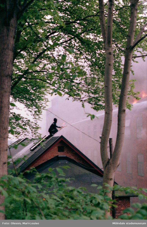 Soab-branden i Stora Götafors den 4 juni 1986. Brandman som sprutar vatten på ett tak från motsatta sidan.