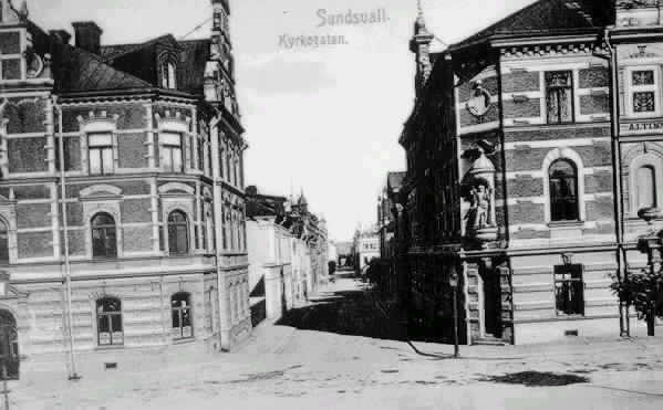"""I förgrunden Skolhusallèn med vy mot Kyrkogatan. Till höger i bild kv Nöjet/ Altinska slöjdskolan och till vänster i bild kv Vinsten/ Prästgården. Text på vykortet """"Sundsvall. Kyrkogatan."""""""