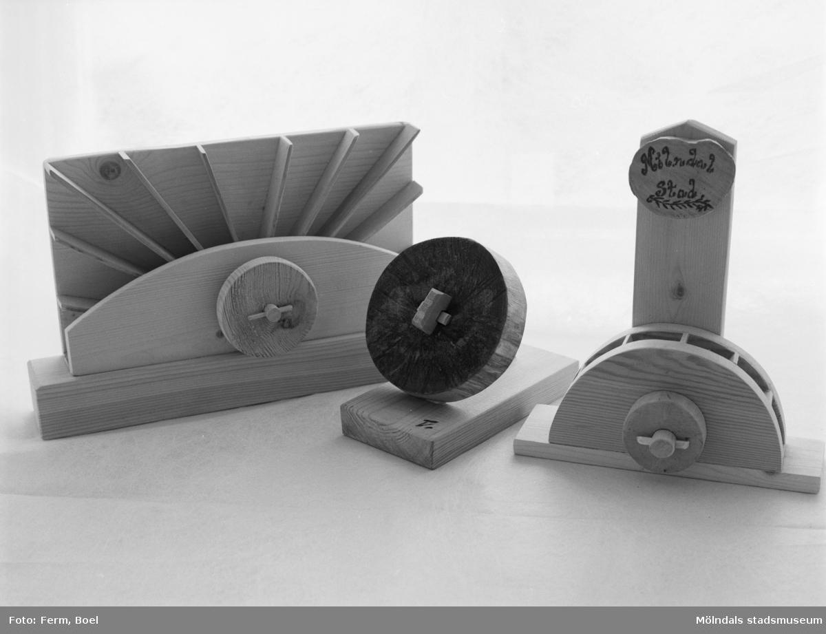 Tre olika träarbeten (brevpress, pennställ) med kvarnhjul som igenkänningstecken. Inlämnat förslag till en tävling 1992 om souvenir för Mölndal.
