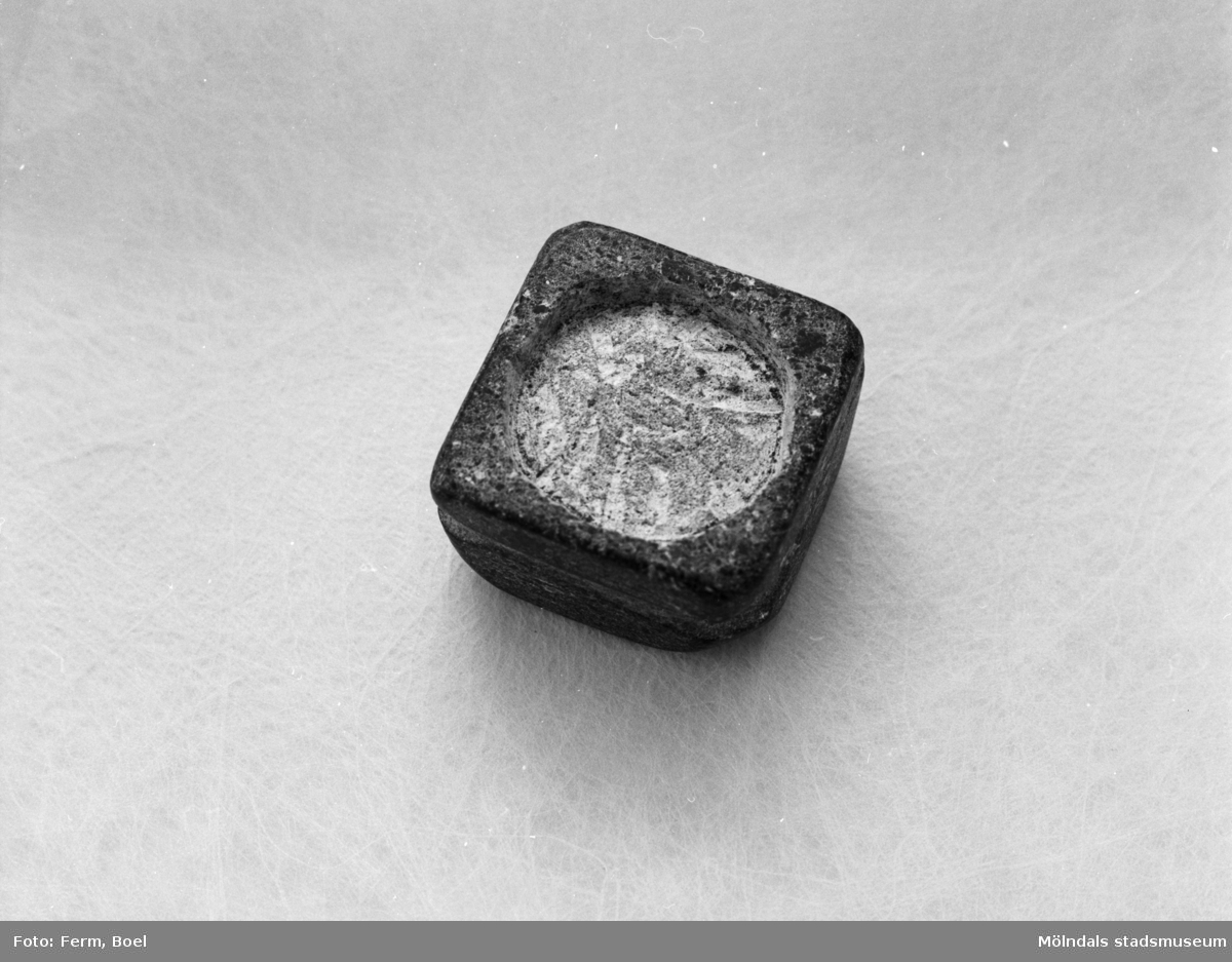 En fyrkantig stenbit som exempelvis kan användas till askfat eller stearinljus. Inlämnat förslag till en tävling 1992 om souvenir för Mölndal.