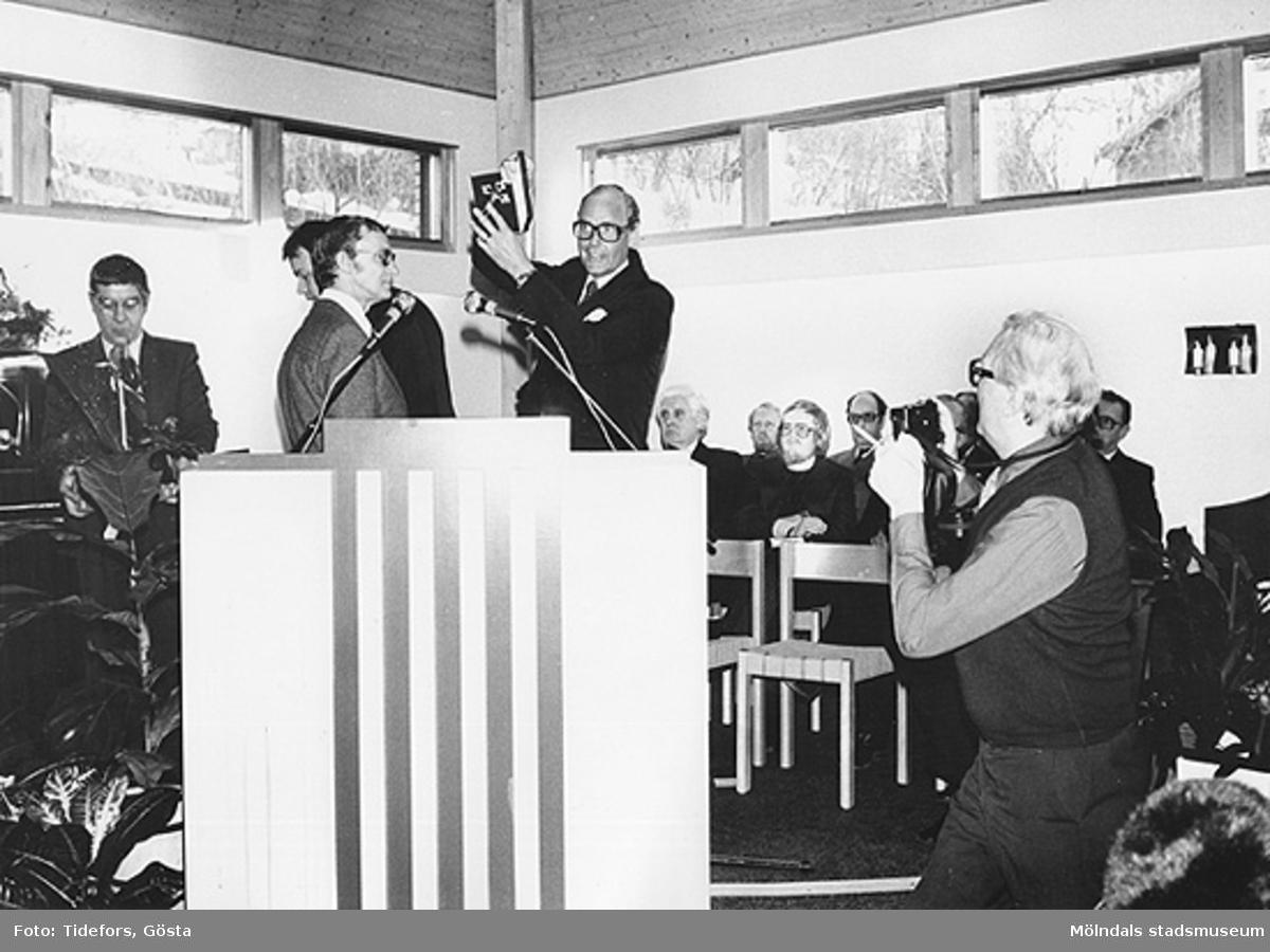 Jon E. Lisshammar fotograferar pastor Holger Sjögreen vid invigningen av Pingstkyrkan i Kållered söndagen den 1/3 1981. Från vänster är Sällskapet Länkarnas ordförande Erik Jörneborn som överlämnar ett silverkors. Den längst t.v är Gösta Gunnarsson. I talarstolen ses Erik Jörneborn och pingstpastor Holger Sjögreen. Till höger om Sjögreen ses pingstpastor Paul Åsberg, en okänd, pastor L. Larsson från Missionskyrkan i Kållered, Ansvarsavdelningschef Harry Lundgren, chefredaktör.