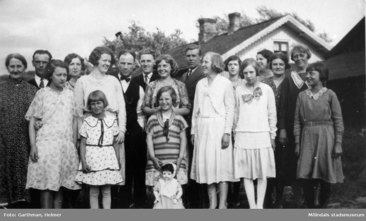 """Helmer Garthmans (givarens far) släkt och bekanta. Mor Isabella fyller 45 år 1932. De står utanför hemmet """"Flackens i Lackarebäck"""". Dembrover och kusinerna hälsar på från USA. Från vänster står givarens mormor Augusta Blomgren, kvinnan bredvid är Märta Garthman och systern Sonja Garthman. Person nr 7 är Gustav Andersson. Från höger, tredje person: Isabella Blomgren-Garthman, fjärde person: Ester Garthman Andersson."""