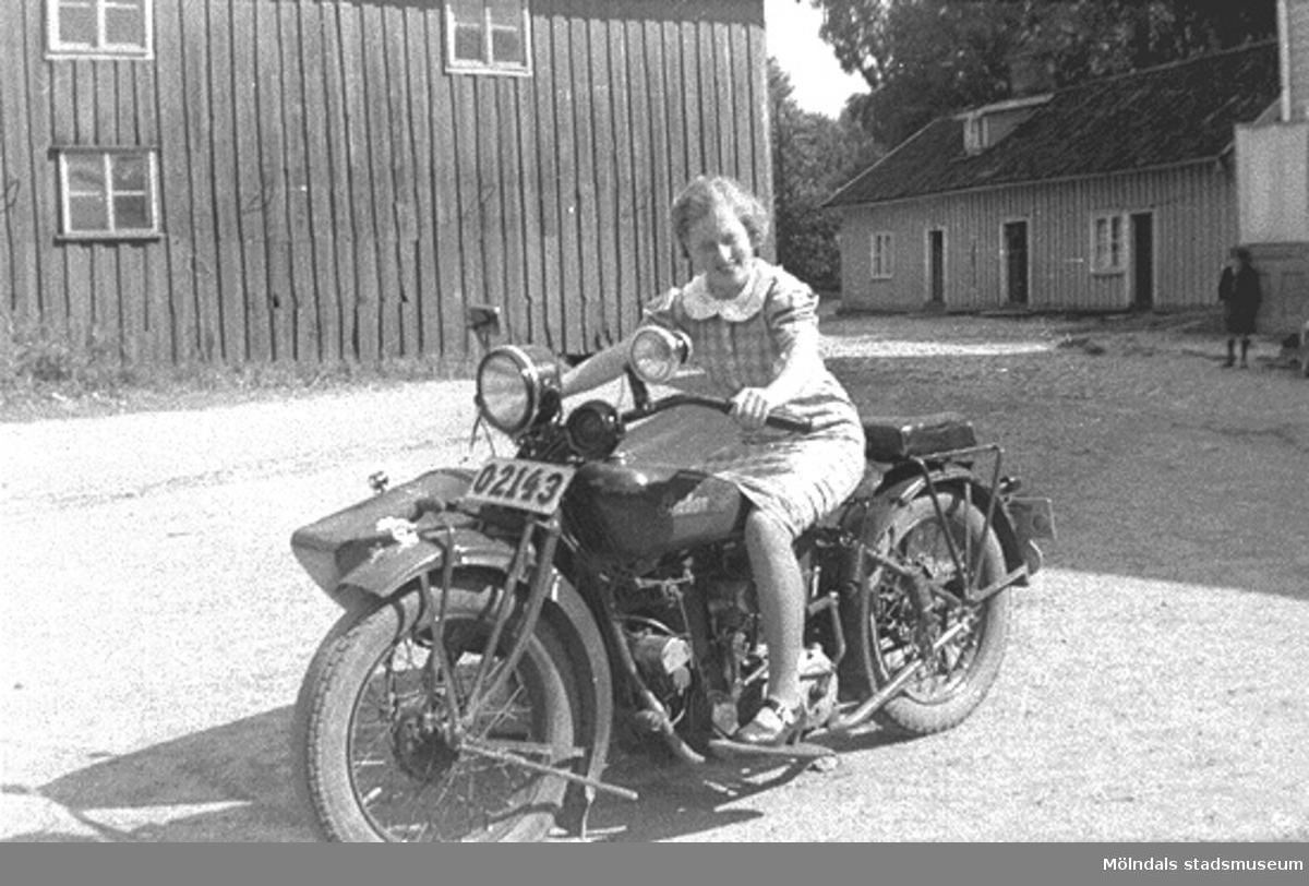 Astrid Karlsson (gift Garthman) grenslar en MC, Indian 1000cc, med sidovagn. Troligtvis är det pojkvännen Helmer Garthmans. Kvarnfallet 31, år 1936.