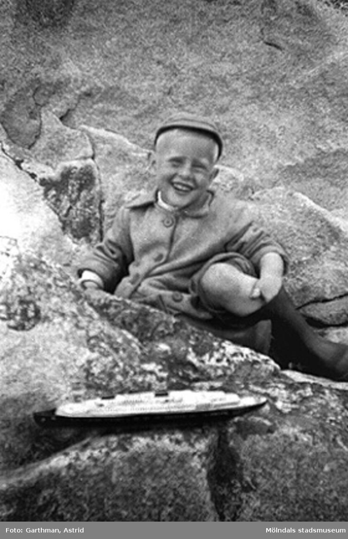 Alf Garthman sitter och leker med sin leksaksbåt bland klipporna vid Näset, 1953-54.