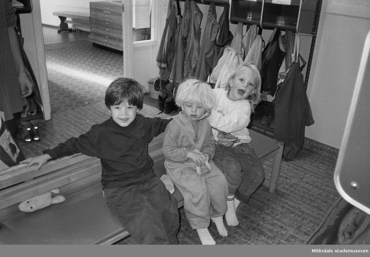 Dagisbarnen Daniel, Rebecka och Malin sitter på en träbänk inomhus, i entrén till Hoppetossan på Katrinebergs daghem. I bakgrunden ser man barnens bås med deras ombytes- och regnkläder.