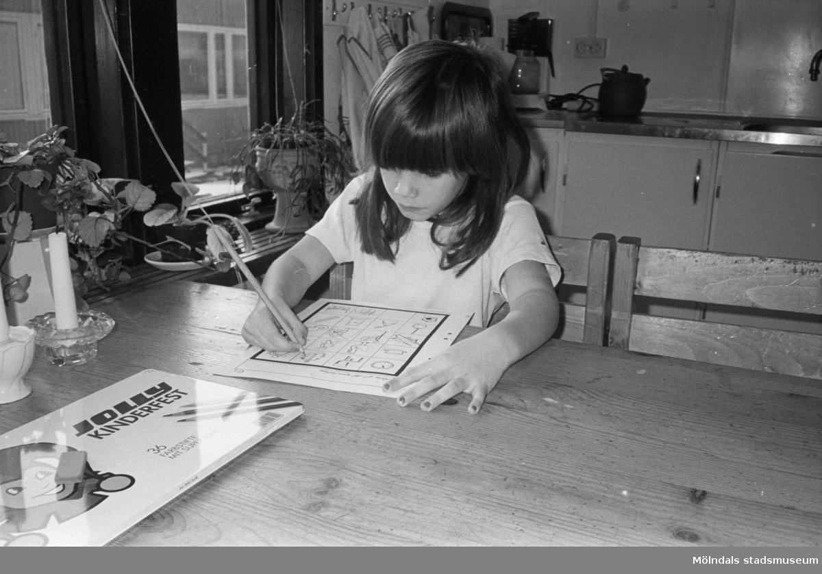 Cecilia sitter vid ett bord och färglägger med hjälp av färgpennor, förtryckta figurer på ett A4-blad. Flickan är mycket koncentrerad. Lunkentussen, Katrinebergs daghem 1992.