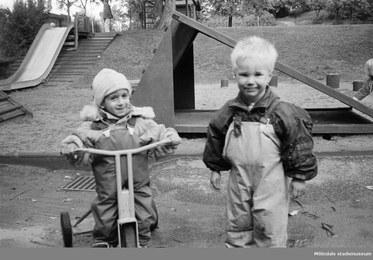 Två små pojkar, tittar leende mot fotografen. De är i lekplatsens sandlåda, iklädda regnkläder. Den högra pojken sitter på en trehjuling och den andre står bredvid. I bakgrunden ser man rutschkanor och klätterställning. Katrinebergs daghem, 1992.