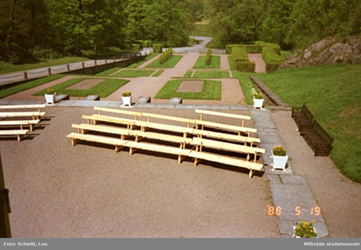 Några bänkar i förgrunden till Gunnebo slott, med parken i bakgrunden.