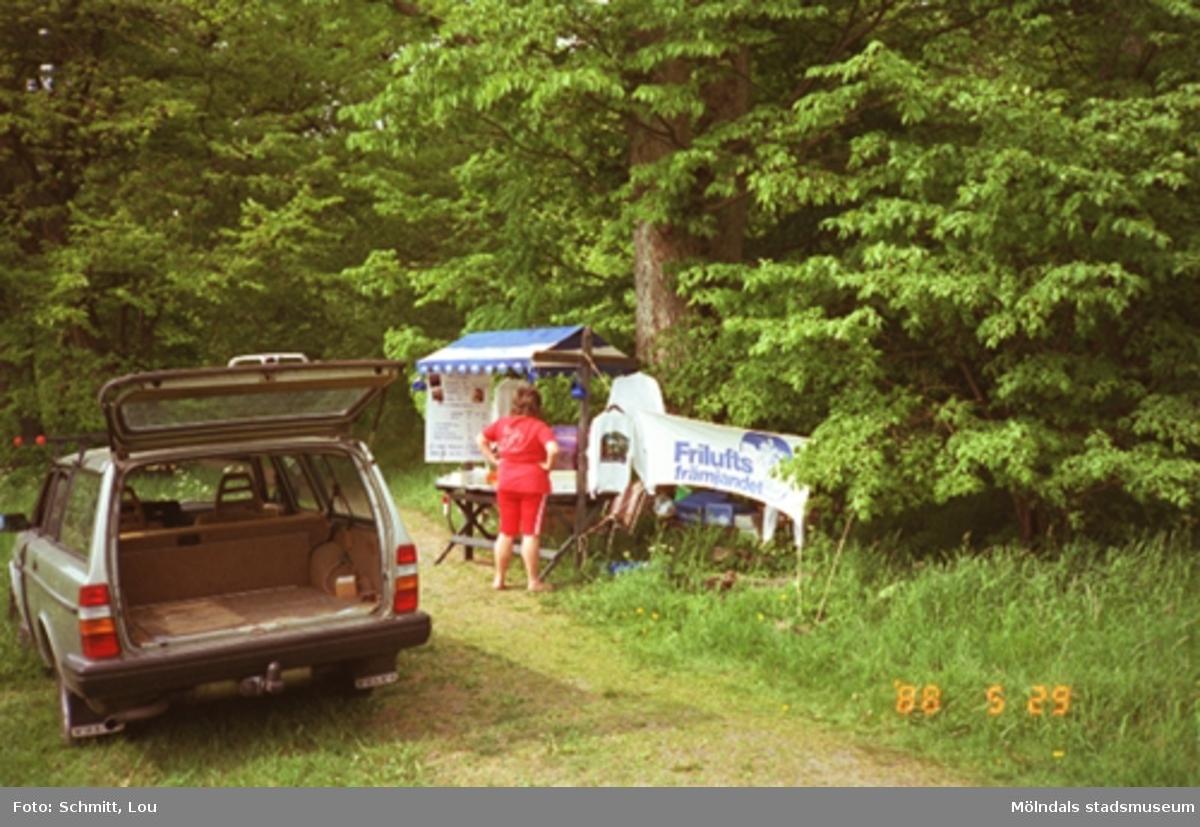 """En rödklädd kvinna står framför ett uppställt stånd med en banderoll som det står """"Friluftsfrämjandet"""" på. Till vänster står en Volvo 245 med öppen, tom baklucka."""