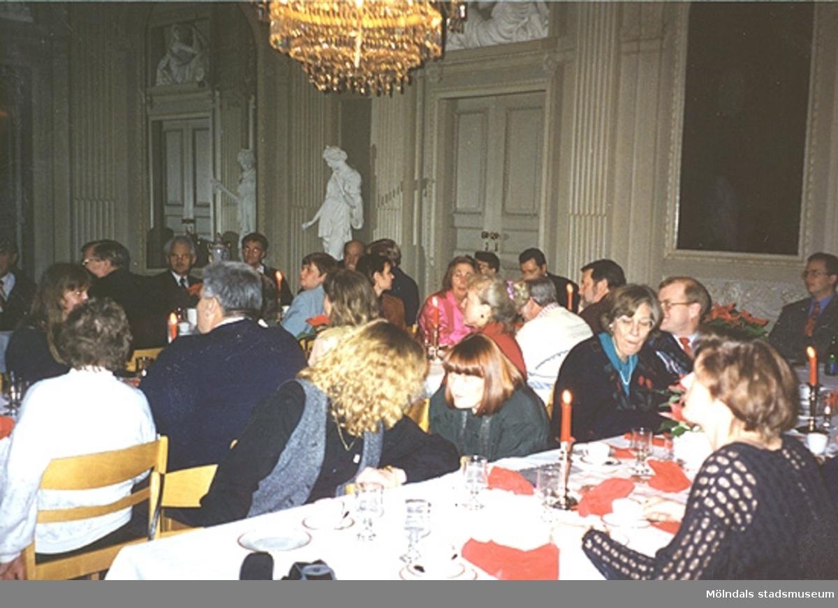 Avtackning och fest i stora salongen på Gunnebo slott av Sten G. Svensson, december 1994. Museichef Mari-Louise Olsson syns i mitten av bilden då hon lutar sig fram och talar med en kvinna.