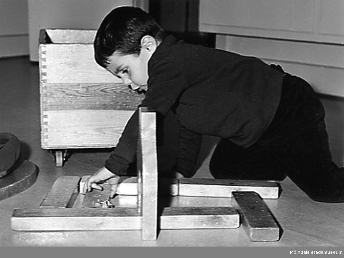 En pojke som leker med byggklossar på golvet vid Holtermanska daghemmet 1953.