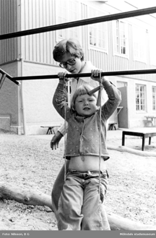Ett barn sitter i ett rep som är fastsatt i en ställning. Bakom barnet står en lärarinna. Holtermanska daghemmet 1973.