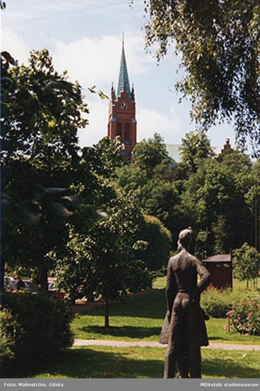 """Vy från stadshusparken mot Fässbergs kyrka, 1996. I förgrunden ses Arvid Bryths (1905-1997) skulptur """"Ungdomssvärmeri""""."""