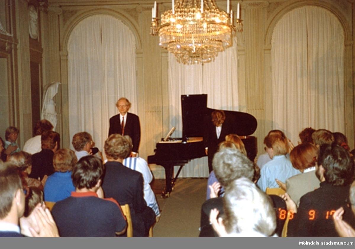 En musikkonsert inne på slottet. En man står vid ett piano, vänd mot publiken.