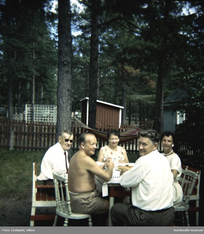 Barbro och Viktor Lindqvist har släktbesök i sommarstugan i Tranviken. Viktor är trolig fotograf. Mannen med bar överkropp är Brage Sjödin från Västerås. Vid hans sida med solglasögon sitter syskonen Sjödins morbror, Otto Lundqvist född i Finland.  Mannen med ryggen åt fotografen är Knut Björk, han har sin hustru på andra sidan bordet, Britta Björk  född Sjödin. Paret Björk har sin sommarstuga i Krokviken.