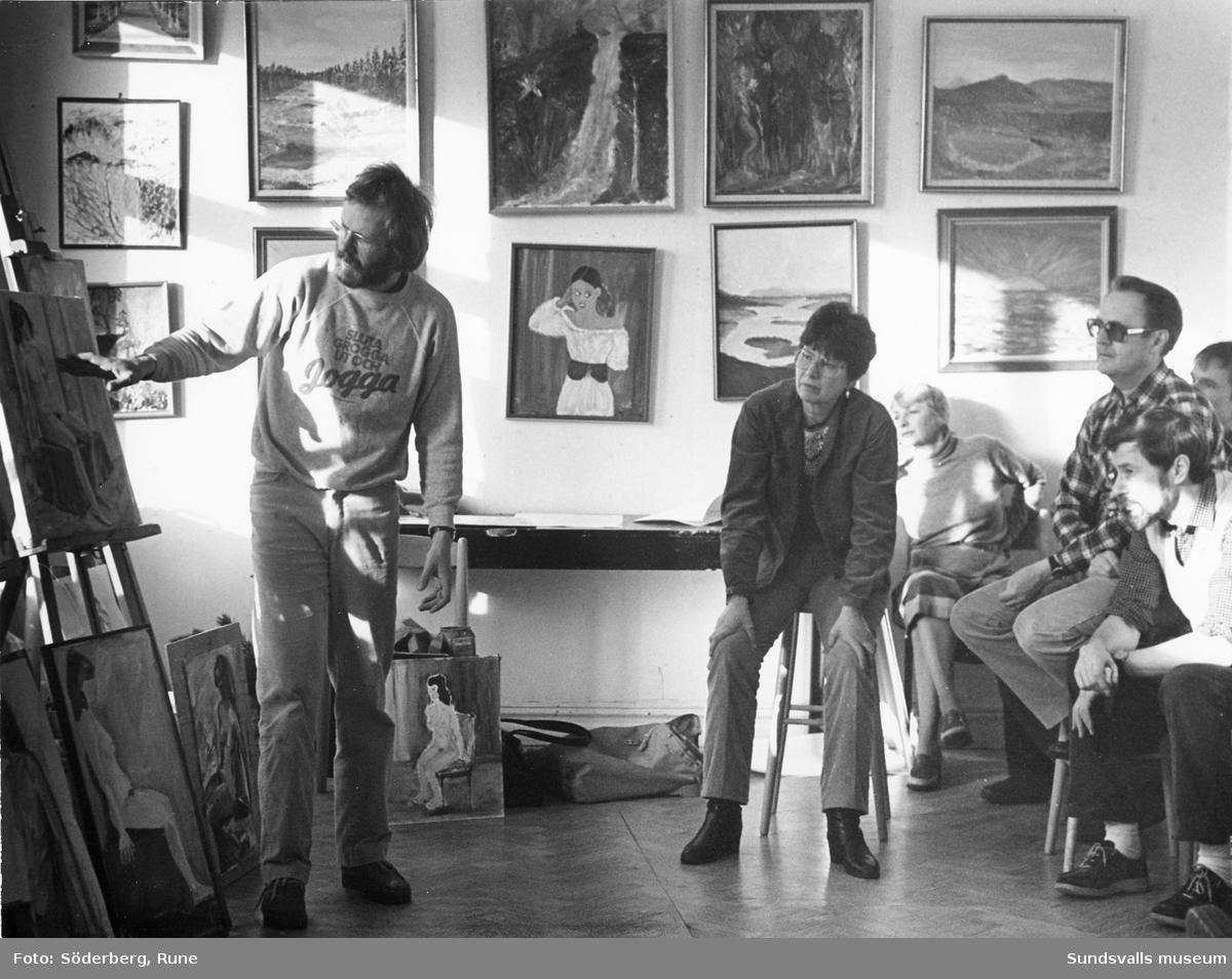 Medlemmar i Kollektivverkstaden i Sundsvall studerar en målning.