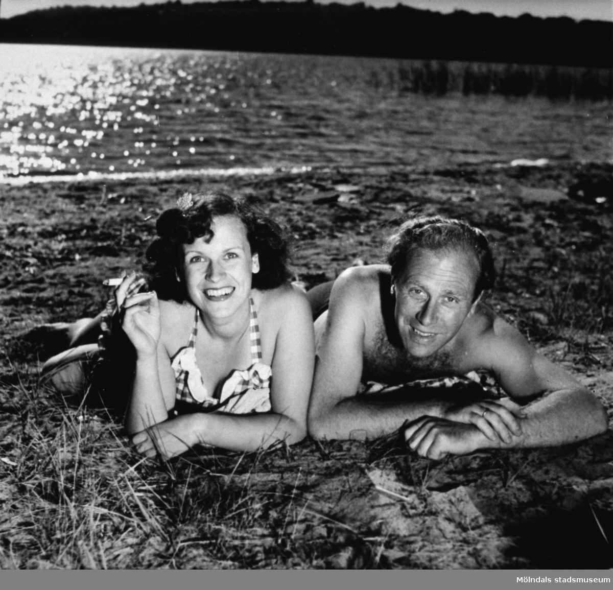 En kvinna och man ligger vid strandkanten V Tulebosjön, cirka 1940-tal.