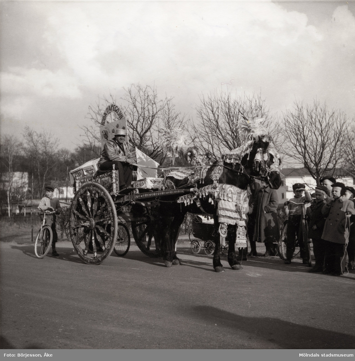 """Motiv från Solängen. Häst med vagn och kusk bär dekorationer. Möjligtvis reklam av något slag? Skylt med texten """"Röda papegojan"""" på vagnen. Barn på cyklar står runt omkring och tittar på. Möjligen Frölundagatan på 1950-60-talet."""