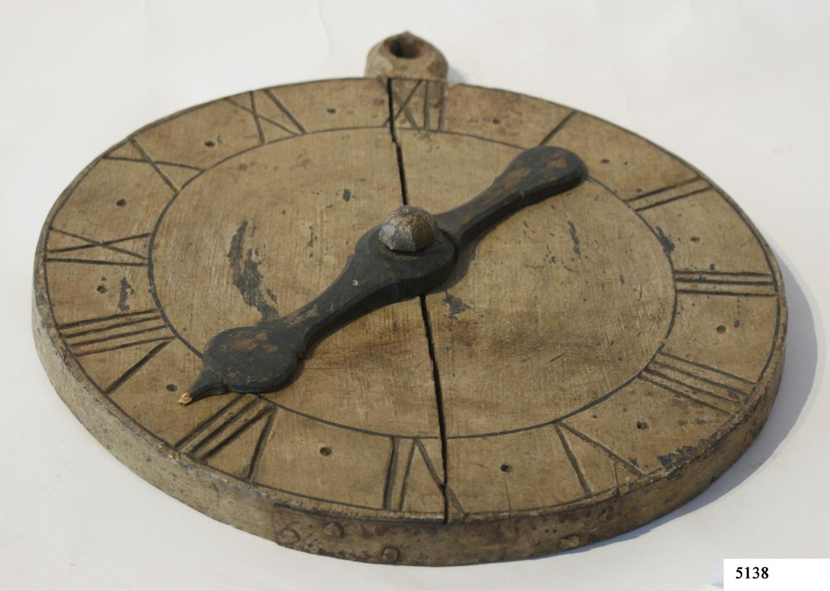 Urtavla av ek med ställbar snidad visare, avsedd att ställas efter timglas. Rund till formen.