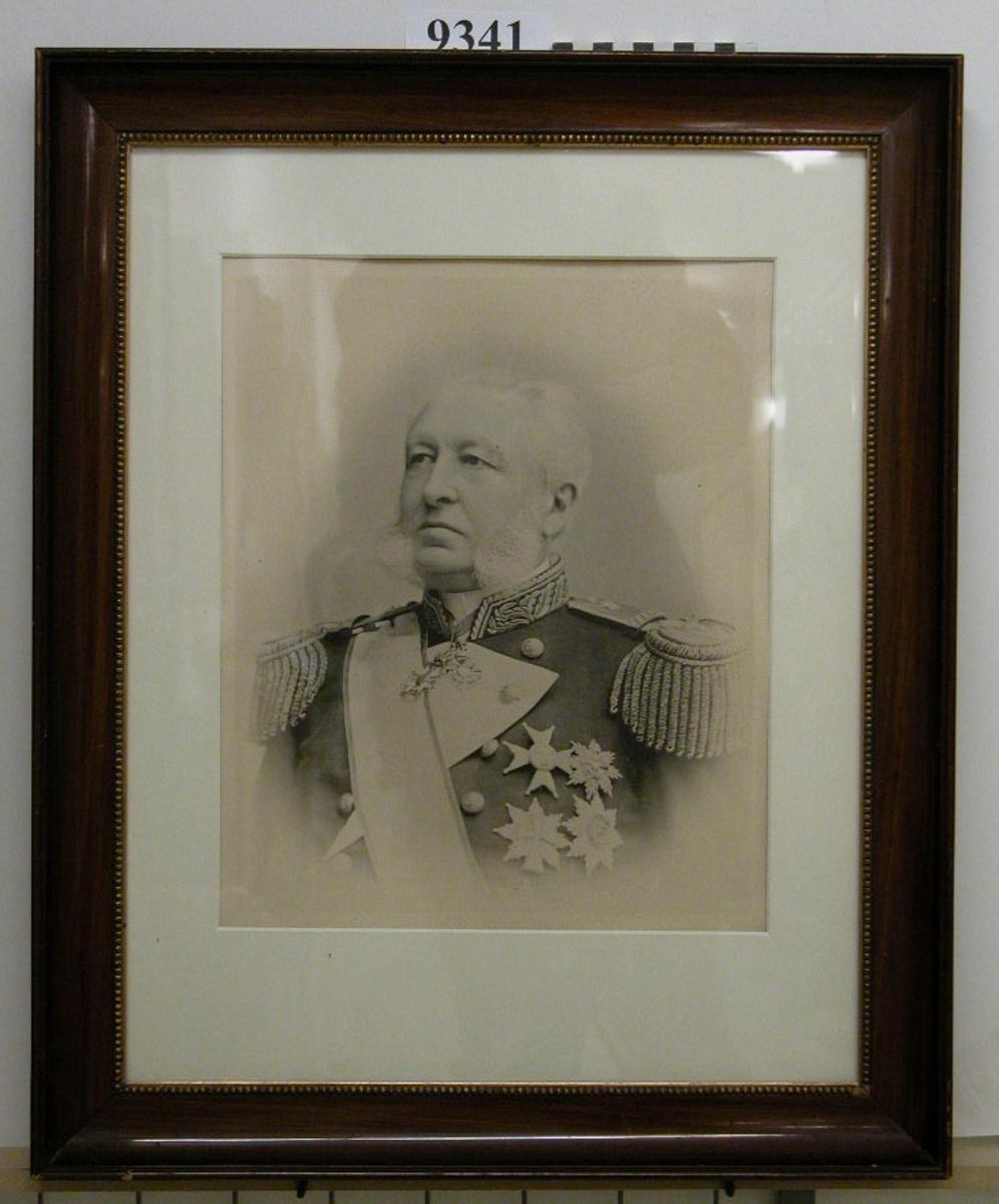 Fotografi inom glas och ram, trä, brun, polerad, med förgylld innerkant. Visar amiral (okänd) i uniform. Neg.nr 4848.
