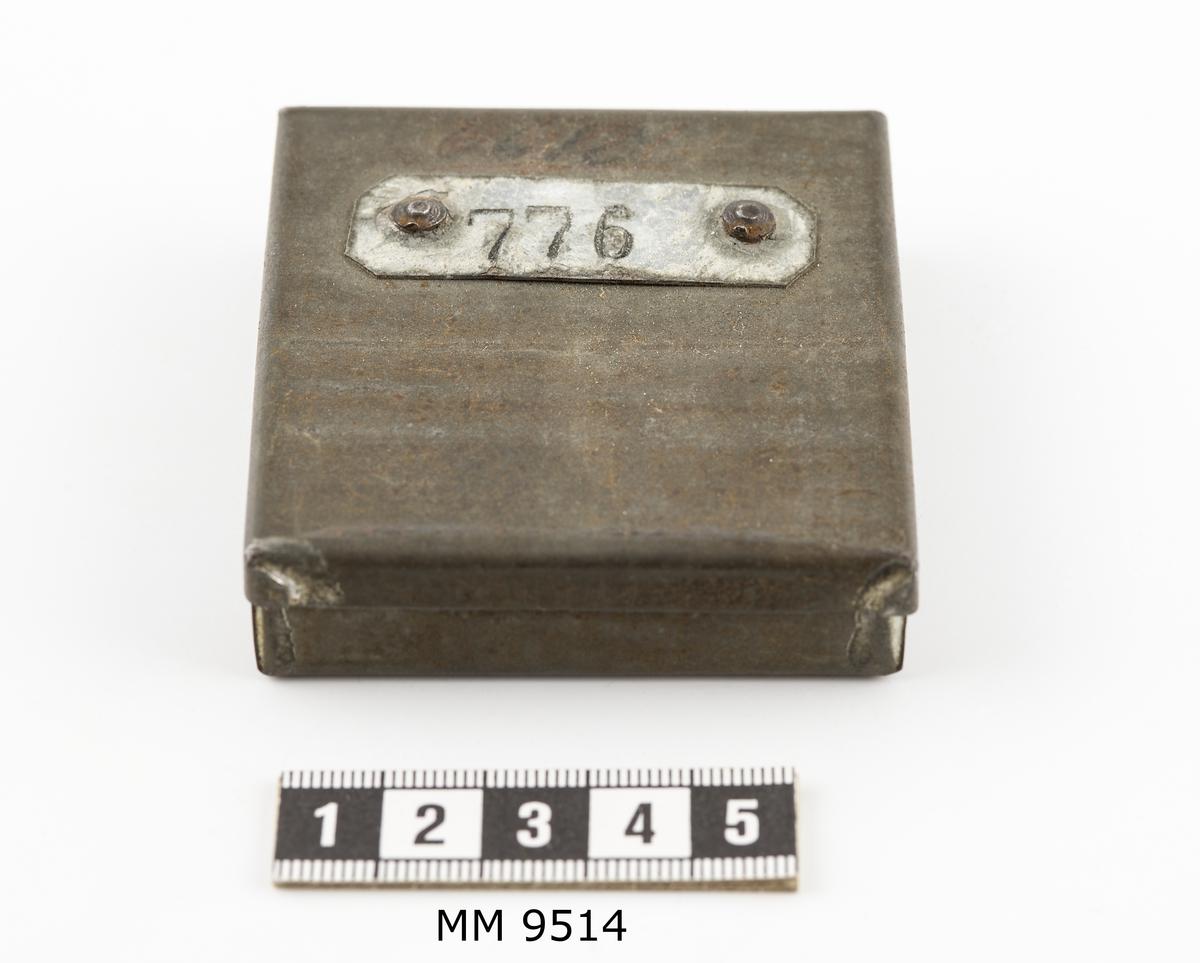 Ask, avlönings-, av bleckplåt. Rektangulär. Asken är in- och utvändigt stämplad med arbetarens nummer, 776, på plåtar av bleck, fastnitade invädigt i botten och utvändigt på locket, samt skrivet med bläck på locket: 6613.