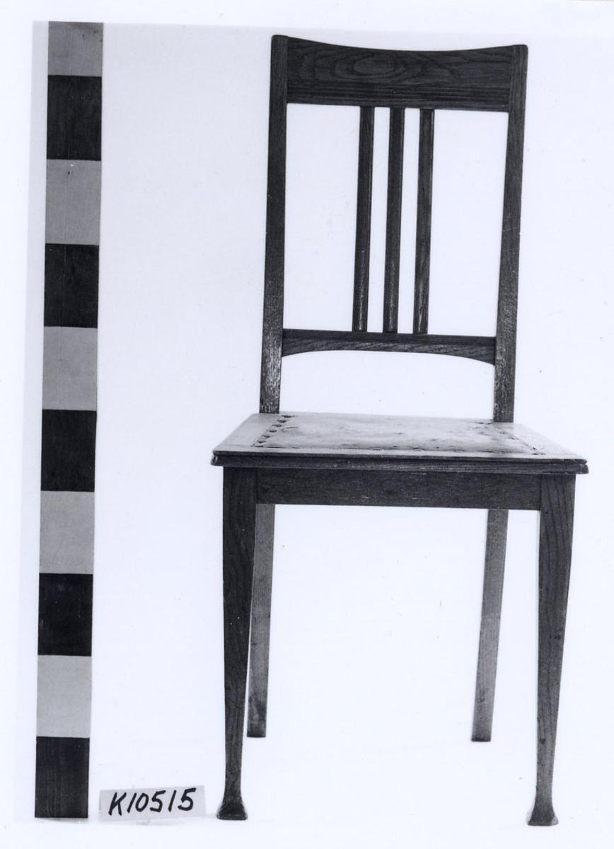 Stol av ek med skinnklädd sits. Fyrsidiga ben, de bakre svängda. Rygg med överstycke samt tre vertikala spjälor från överstycke till tvärslå.
