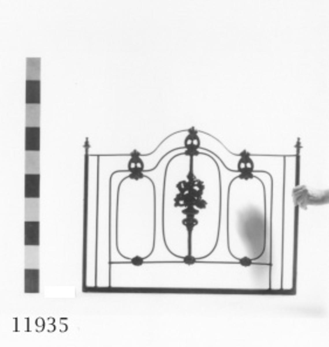 Sänggavel av halv- och rundjärn. Försedd med gjutna ornament i form av blad- och blommönster i relief samt två svarvade knoppar av mässing. Svartmålad.