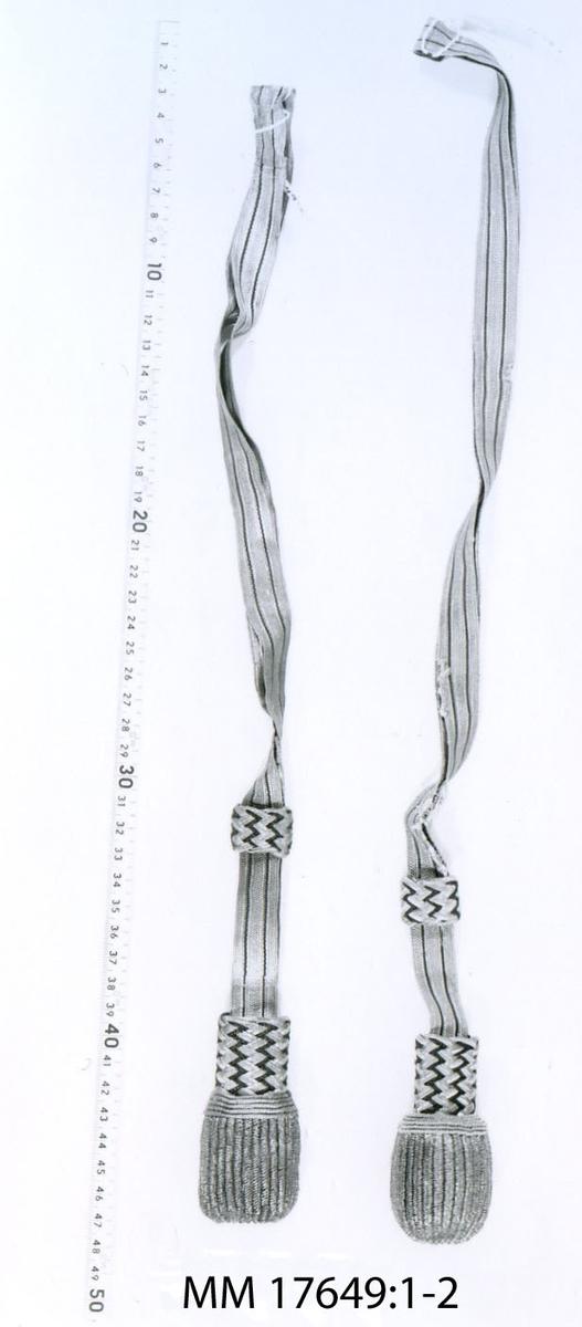 Portepé m/1878, bestående av band och tofs av vävd guldtråd med inslag av silkesränder, på tofs och hälla ett flätat mönster av guld och silke.