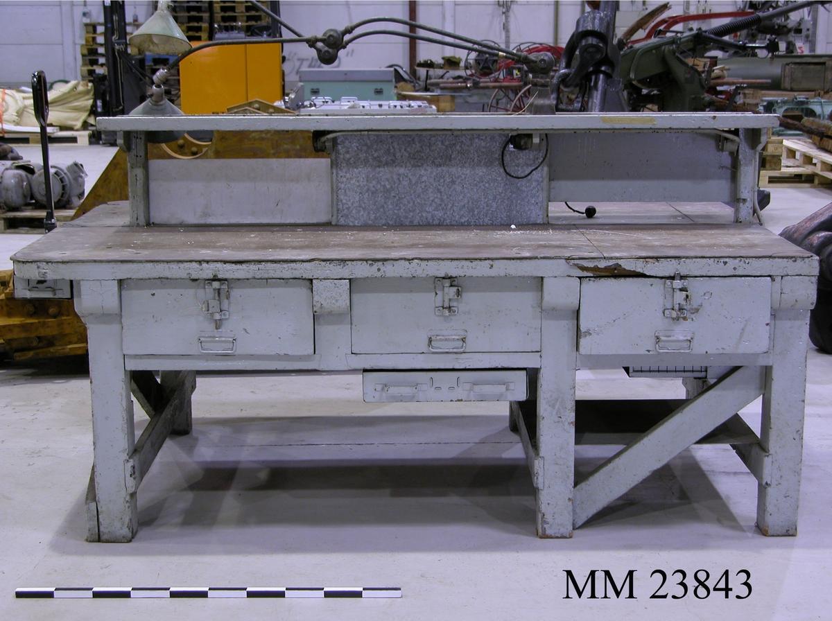 """Arbetsbänk i trä. Målad i gråblå färg. Bänken är försedd med 6 stycken trälådor samt 5 stycken metallådor. Trälådorna kan låsas med hänglås. Två stycken arbetslampor finns monterade på arbetsbänken, i utfällt tillstånd når dessa 1030 mm. De är märkta: """"TRIPLEX-PENDEL PATENT MADE IN SWEDEN"""". Där finns märken på bänken efter tidigare lampor. Två stycken eluttag finns på undersidan. I en av lådorna återfanns en """"Verktygsbok"""" tillhörandes bänken. I boken kan man på sista sidan utläsa att bänken använts av 3755 Källsson, 3432 (otydligt, kanske Källsson igen), 3778 Andersson samt 3395 Erik Strindhagen.  Det finns ett upphöjt mitträcke på bänken som mäter: Höjd: 330 millimeter och bredd: 330 millimeter."""
